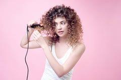 Красивая молодая женщина делая скручиваемости с завивая утюгом Стоковая Фотография