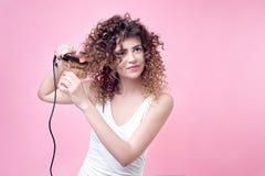 Красивая молодая женщина делая скручиваемости с завивая утюгом Стоковое Изображение