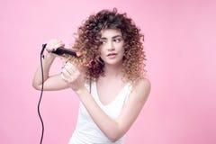 Красивая молодая женщина делая скручиваемости с завивая утюгом Стоковые Фотографии RF