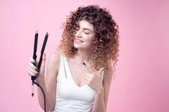 Красивая молодая женщина делая скручиваемости с завивая утюгом Стоковая Фотография RF