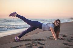 Красивая молодая женщина делая тренировку на песчаном пляже, здоровом стоковая фотография rf