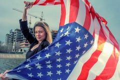 Красивая молодая женщина держа муху американского флага ветром стоковая фотография