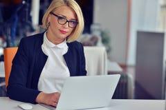 Красивая молодая женщина держа руки на подбородке и усмехаясь пока сидящ на ее месте службы Стоковое Фото