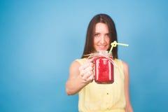 Красивая молодая женщина держа smoothie клубники на голубой предпосылке Здоровая органическая концепция пить Люди на диете Стоковые Изображения