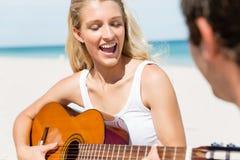 Красивая молодая женщина играя гитару на пляже Стоковое Изображение RF