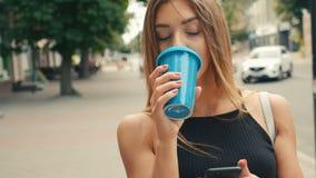 Красивая молодая женщина идя в город Используя ее мобильный телефон Печатать сообщение Усмехаться счастливо Выпивать очень вкусны сток-видео