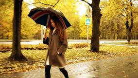 Красивая молодая женщина идя с зонтиком вдоль переулка осени на дождливый день Стоковые Фото