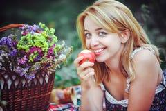 Красивая молодая женщина имея пикник в сельской местности Счастливый уютный день outdoors открыто Усмехаясь женщина есть яблоко,  Стоковые Изображения