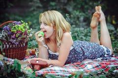 Красивая молодая женщина имея пикник в сельской местности Счастливый уютный день outdoors открыто Усмехаясь женщина есть яблоко,  Стоковые Фото