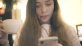 Красивая молодая женщина использует ее смартфон пока имеющ чай или кофе в кафе сток-видео