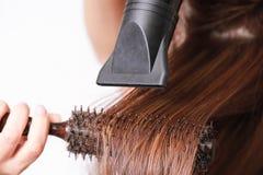 Красивая молодая женщина использует фен для волос стоковое фото rf
