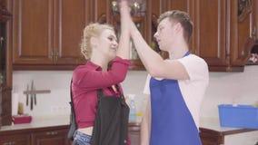 Красивая молодая женщина и человек в рисбермах принимая перчатки и максимум 5 Семья заканчивая чистку дома акции видеоматериалы