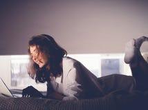 Красивая молодая женщина лежа на кровати с тетрадью Стоковое Фото