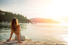 Красивая молодая женщина наслаждаясь заходом солнца на море Стоковые Изображения