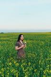 Красивая молодая женщина на заходе солнца в поле Стоковая Фотография