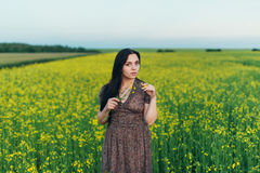 Красивая молодая женщина на заходе солнца в поле Стоковые Изображения RF