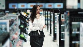 Красивая молодая женщина на косметических взглядах магазина на камере и улыбках, замедленном движении сток-видео