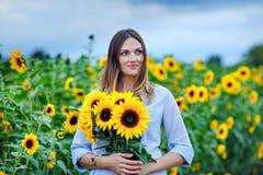 Красивая молодая женщина на поле солнцецвета с букетом цветет Счастливая девушка на день захода солнца лета стоковое изображение rf