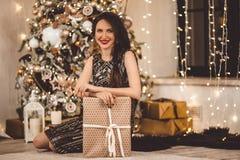 Красивая молодая женщина носит роскошное платье на фоне рождественской елки с подарочной коробкой стоковые фото