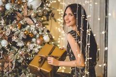 Красивая молодая женщина носит роскошное платье на фоне рождественской елки с подарочной коробкой стоковые фотографии rf