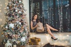 Красивая молодая женщина носит роскошное платье сидя на силле окна украшенном с гирляндами стоковые фото