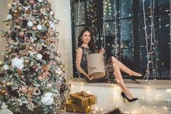 Красивая молодая женщина носит роскошное платье сидя на силле окна украшенном с гирляндами стоковые изображения rf