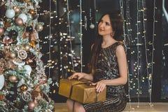 Красивая молодая женщина носит роскошное платье сидя на силле окна украшенном с гирляндами стоковое фото rf