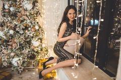 Красивая молодая женщина носит роскошное платье сидя на силле окна украшенном с гирляндами стоковые фотографии rf
