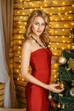 Красивая молодая женщина около Нового Года рождественской елки ждать и праздников рождества стоковое фото
