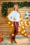 Красивая молодая женщина около Нового Года рождественской елки ждать и праздников рождества стоковое изображение