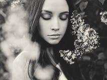 Красивая молодая женщина окруженная цветками сирени Стоковое Изображение