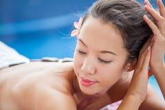 Красивая молодая женщина ослабляя на курорте бассейна здоровья лежа вниз h Стоковые Изображения RF