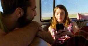 Красивая молодая женщина отправляя SMS на мобильном телефоне в фургоне 4k сток-видео