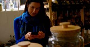 Красивая молодая женщина отправляя SMS на мобильном телефоне 4k видеоматериал