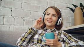 Красивая молодая женщина поет слушать к любимой песне через наушники и держать чашку горячего чая самомоднейше акции видеоматериалы