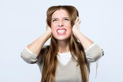 Красивая молодая женщина покрывая ее уши над серой предпосылкой Стоковое Изображение RF