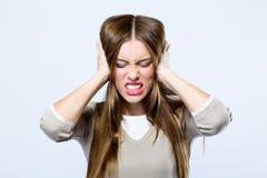 Красивая молодая женщина покрывая ее уши над серой предпосылкой Стоковое Изображение