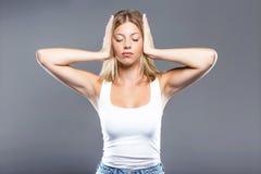 Красивая молодая женщина покрывая ее уши над серой предпосылкой Стоковые Изображения RF