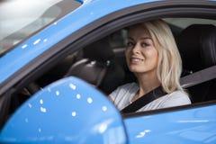 Красивая молодая женщина покупая новый автомобиль на дилерских полномочиях стоковое фото rf