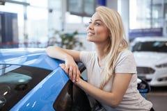 Красивая молодая женщина покупая новый автомобиль на дилерских полномочиях стоковое изображение