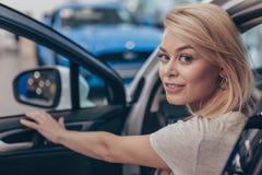 Красивая молодая женщина покупая новый автомобиль на дилерских полномочиях стоковое изображение rf