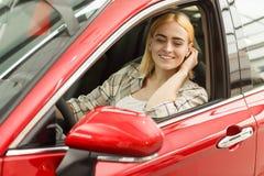 Красивая молодая женщина покупая новый автомобиль на дилерских полномочиях стоковая фотография