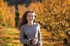 Красивая молодая женщина представляя в поле осени день солнечный Рыжеволосый подросток стоковое фото rf