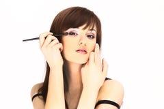 Красивая молодая женщина прикладывая косметическую кисть стоковое фото