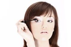 Красивая молодая женщина прикладывая косметическую кисть стоковые фото