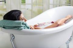 Красивая молодая женщина принимает ванну молока стоковые изображения rf