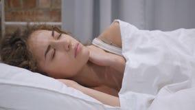 Красивая молодая женщина при боль шеи пробуя спать в кровати сток-видео