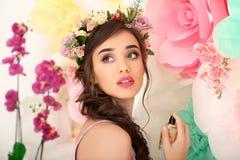 Красивая молодая женщина при бутылка флористического дух стоя близко украшенная стена Стоковое Изображение
