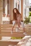 Красивая молодая женщина при закрытые глаза сидя на стенде с роскошной сумкой стоковые изображения rf