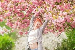 Красивая молодая женщина при красные волосы имея потеху стоя в дереве вишневого цвета стоковые изображения